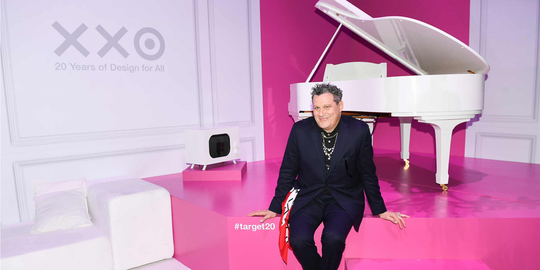 Isaac Mizrahi sits on a pink and white stage in front of a white piano