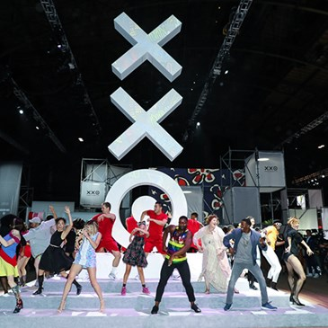A brightly lit stage with 20th Anniversary Collection logo and dancers