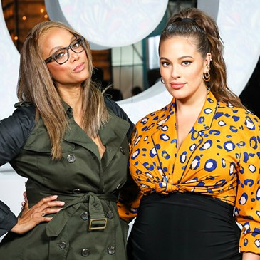 Tyra Banks in a green dress and Ashley Graham in a leopard print top and black skirt pose together