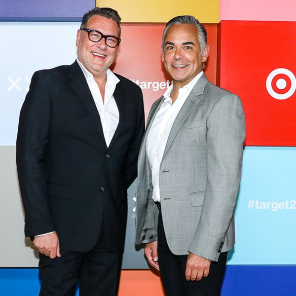 Mark Tritton and Rick Gomez stand together in front of a wall of designer logos
