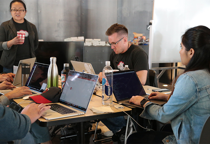 A man and a woman sit at a long table coding on their laptops while another woman watches, holding a cup. The hands of other team members and their laptops are visible on the other side of the table.