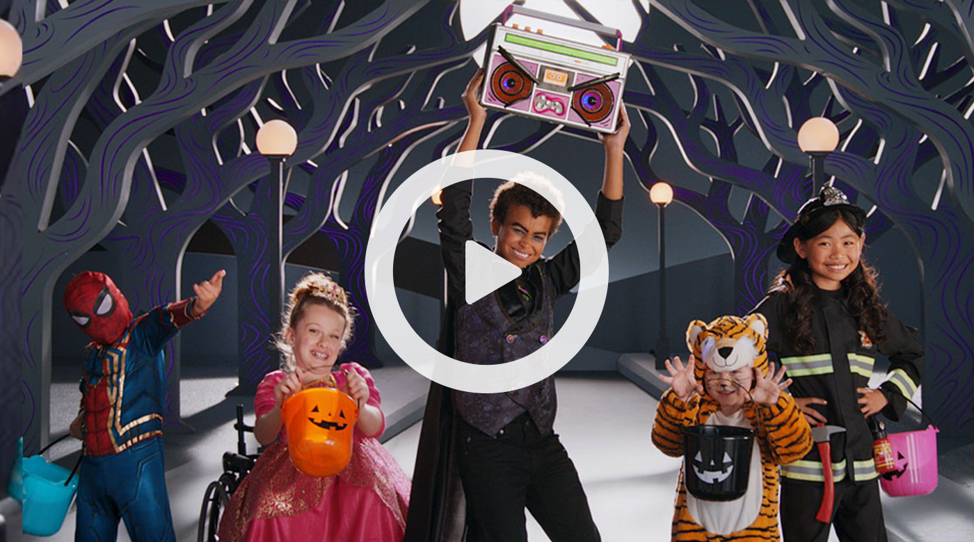 A group of kids in costumes, including a vampire holding a boom box, get ready to dance