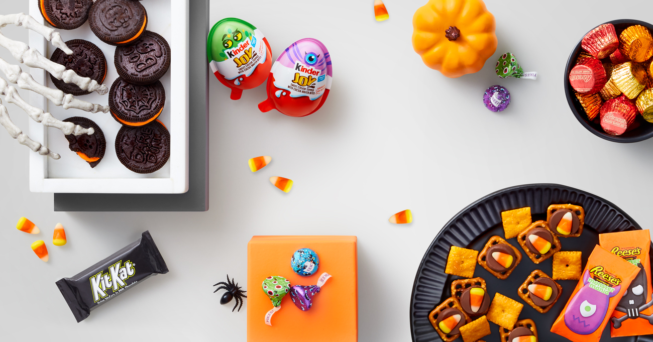 A skeleton hand reaches for an Oreo, surrounded by more Halloween treats