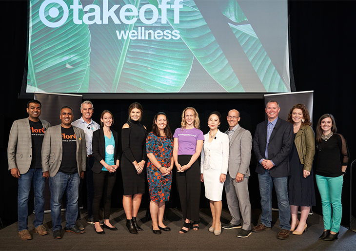 Twelve men and women representing the startups taking part in the accelerator stand onstage together in front of a screen that reads 'Target takeoff wellness""