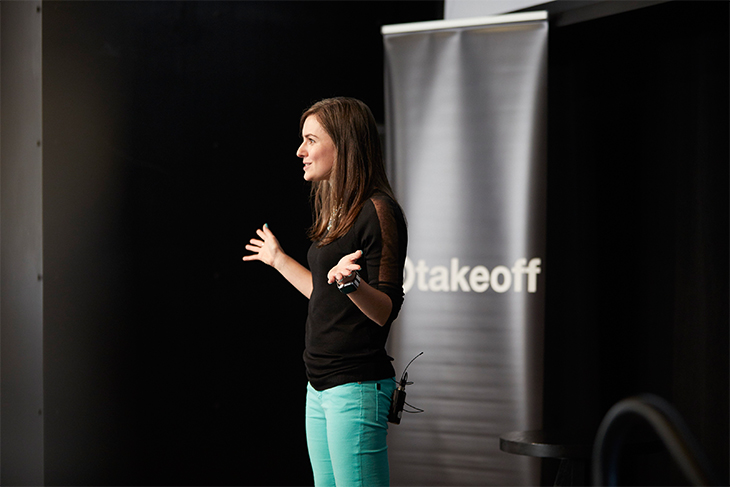 A brunette woman wearing a black top and mint green pants stands onstage with her arms outstretched. Behind her is a black pillar with white text that reads: 'Target Takeoff'