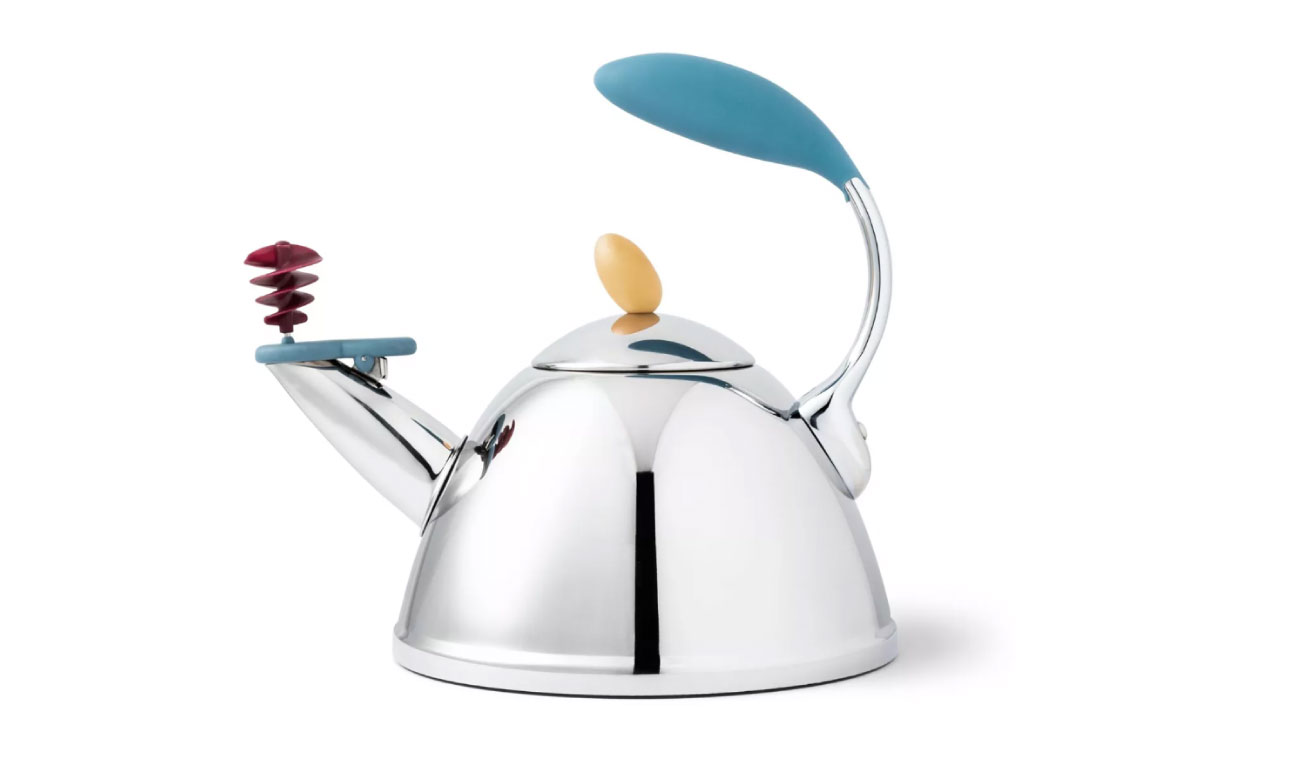 A silver tea kettle with red, yellow and aqua features including a curved handle