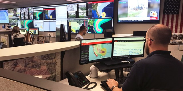 a man looks at computer screens with hurricane projections on it, multiple screens in the background