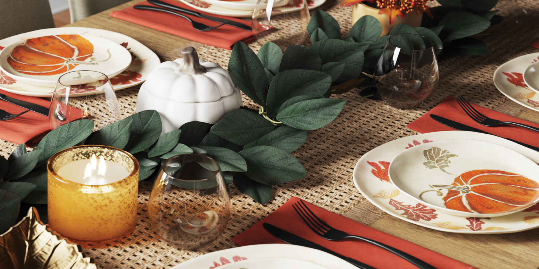A tablescape featuring candles, pumpkins, greenery and more