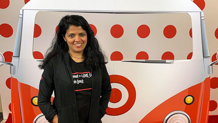 an Indian woman stands in front of a photo backdrop with a bus and bullseye logos