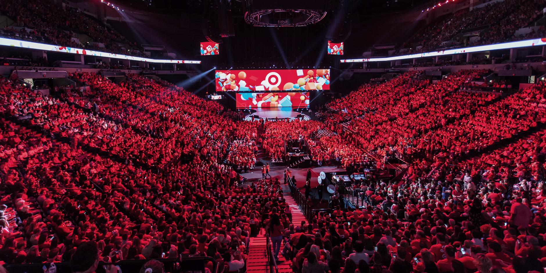 A sea of team members in red and khaki fill the seats at the brightly-lit Target Center