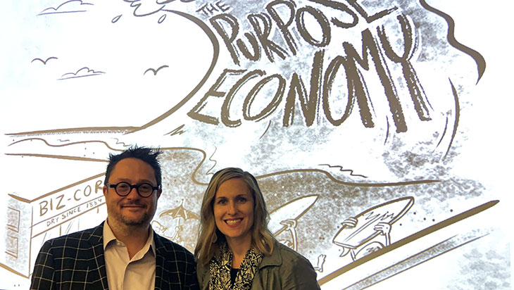 "a man and woman stand in front of a graphic with ""the purpose economy"""