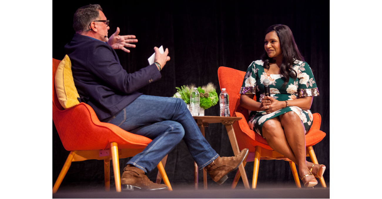 Mark Tritton and Mindy Kaling sit in orange chairs having a conversation on stage