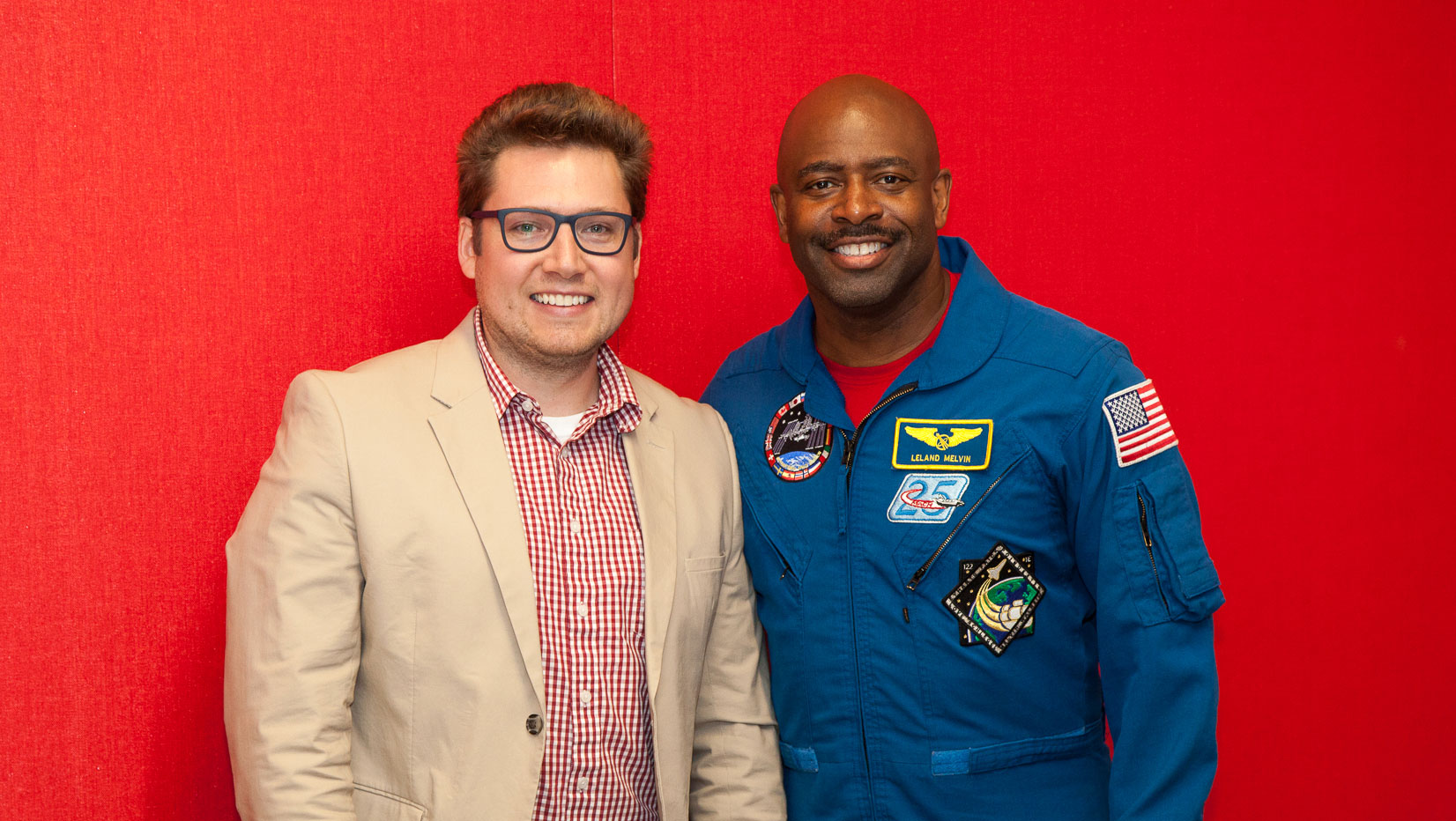 two men stand in front of a red background, one (Leland Melvin) is wearing an astronaut uniform