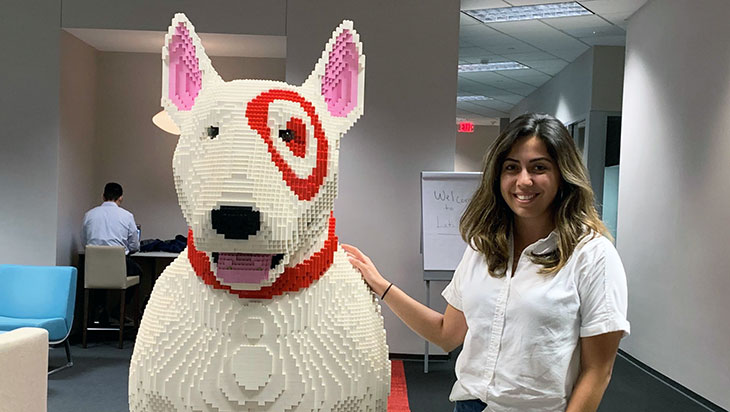 a female stands next to a bullseye dog made out of legos