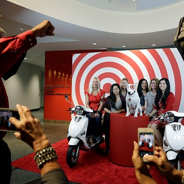 A group of team members pose on red and white scooters against a bullseye backdrop while photographe