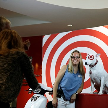 A team member poses with Bullseye the dog in front of a white scooter and red and white logo backdro