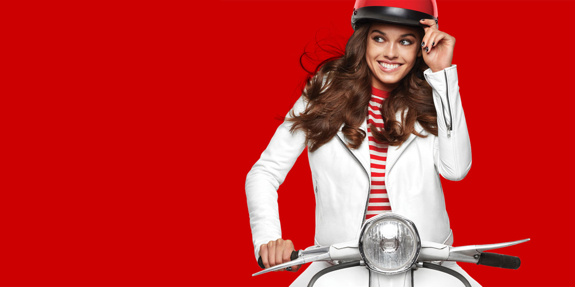 A woman wearing a red helmet and white top rides a moped