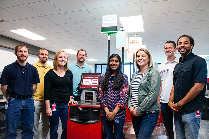A team of engineers gathered around a self-checkout test machine in their workspace.
