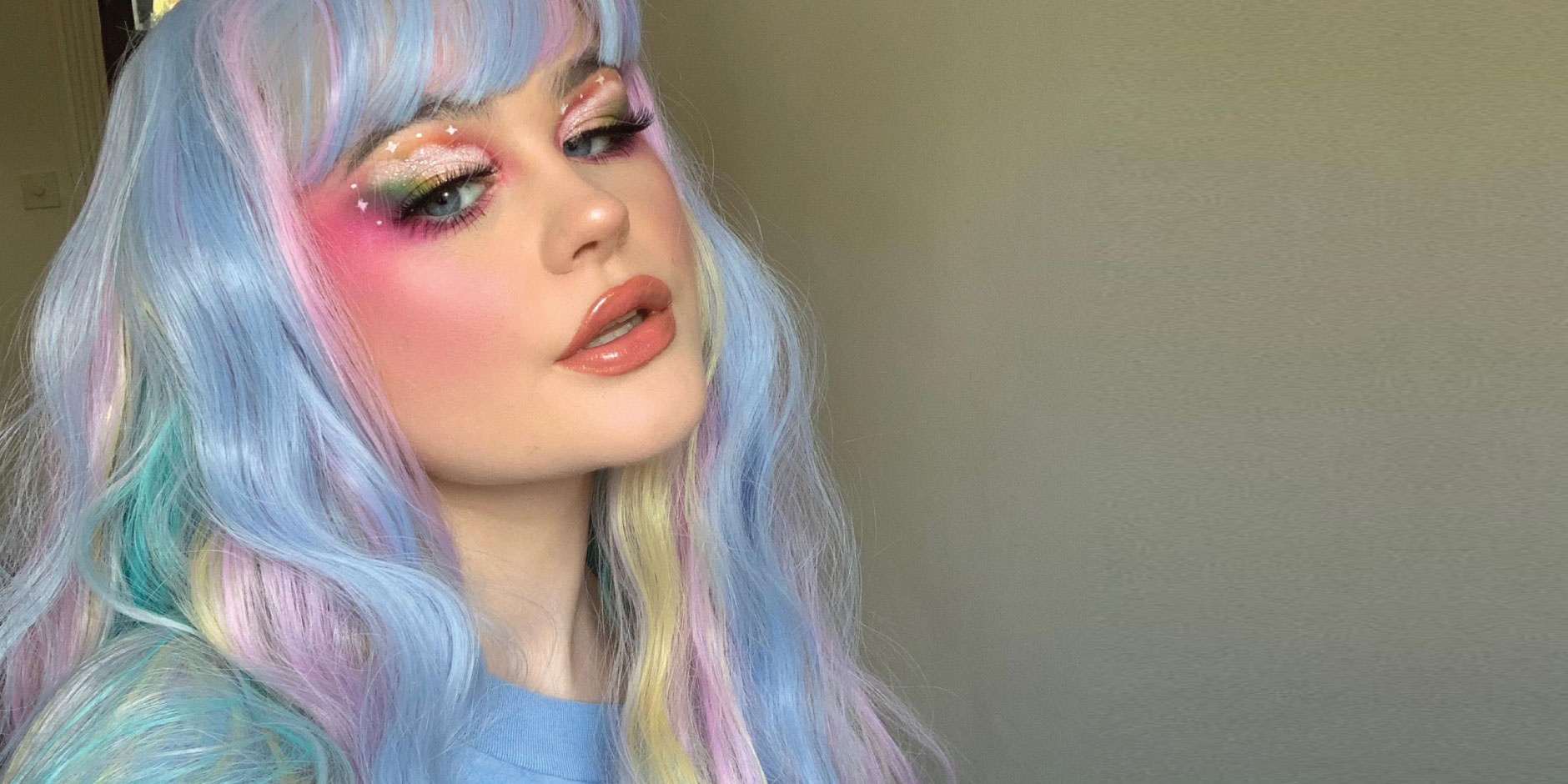 A woman with rainbow pastel hair shows off elaborate unicorn face makeup