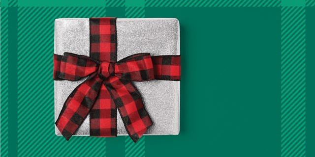 A silver wrapped gift with a red bow is shown against a green plaid background