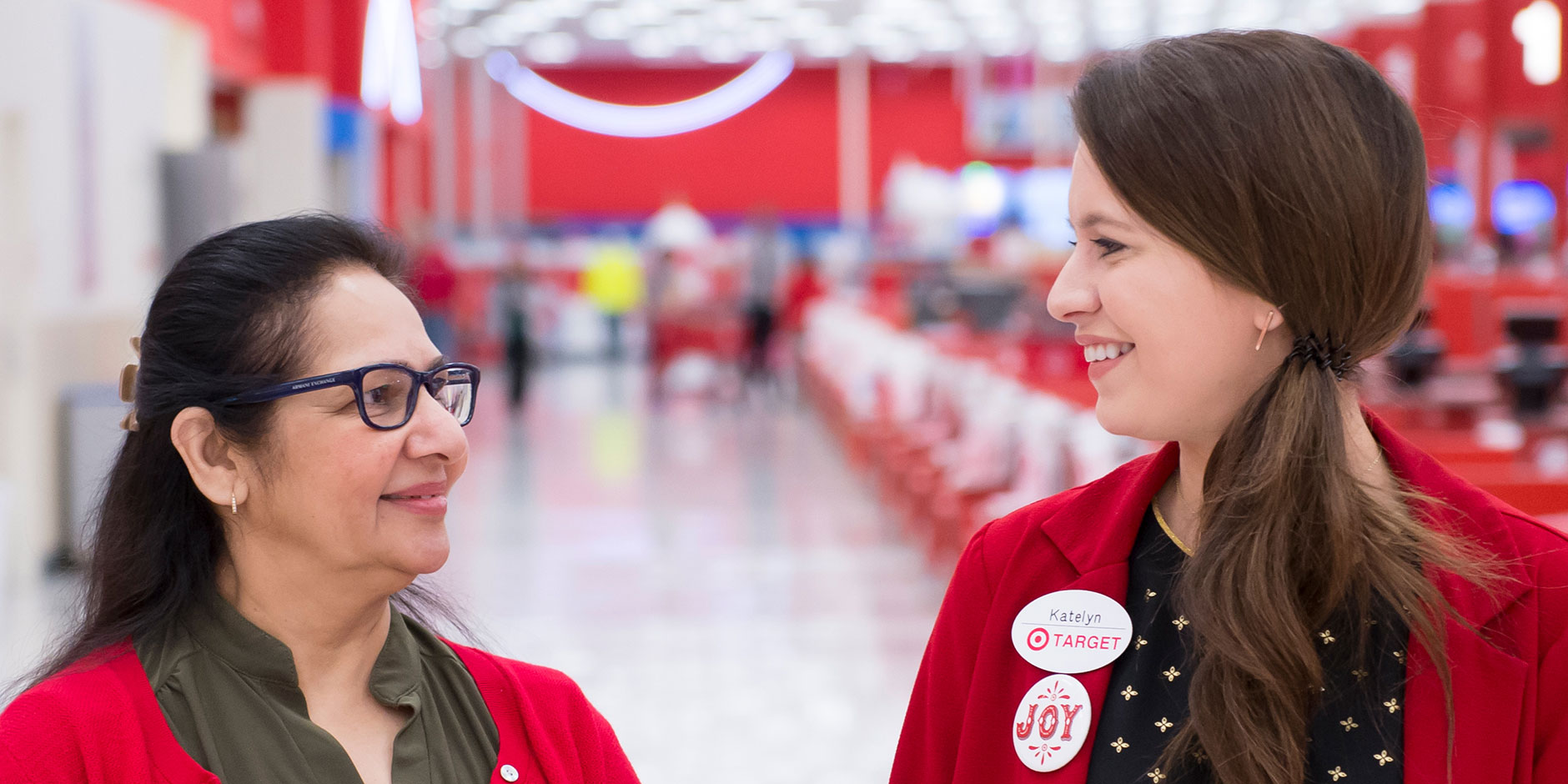 A close-up of two team members smiling at each other and standing in a Target aisle
