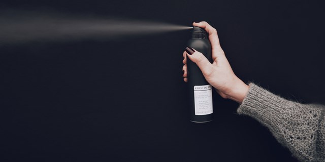a hand holds a black bottle of hairspray on a black background
