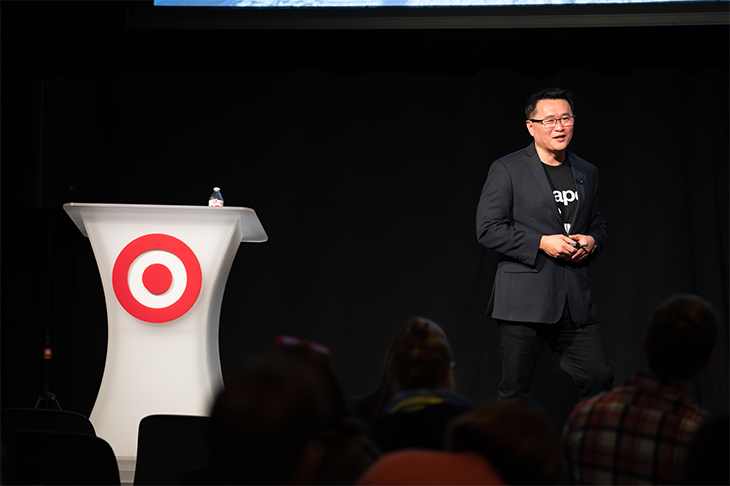 Gene stands onstage in a black jacket and tee next to a white podium with red Bullseye logo