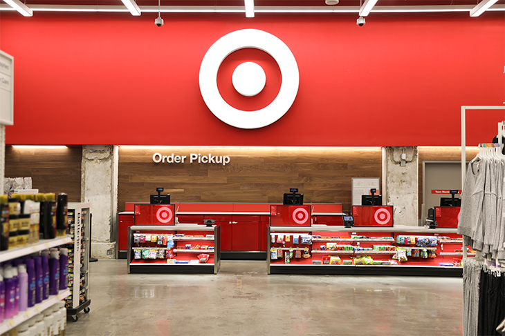 The Order Pickup counter inside a Target store, against a red wall with white bullseye logo and product displays