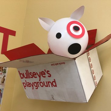 white bullseye dog peeks out of a white box labeled 'bullseye's playground'