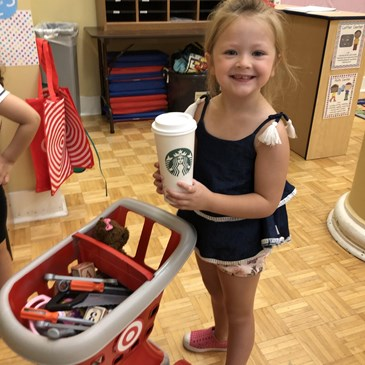 young girl smiles and holds a coffee cup with a shopping cart