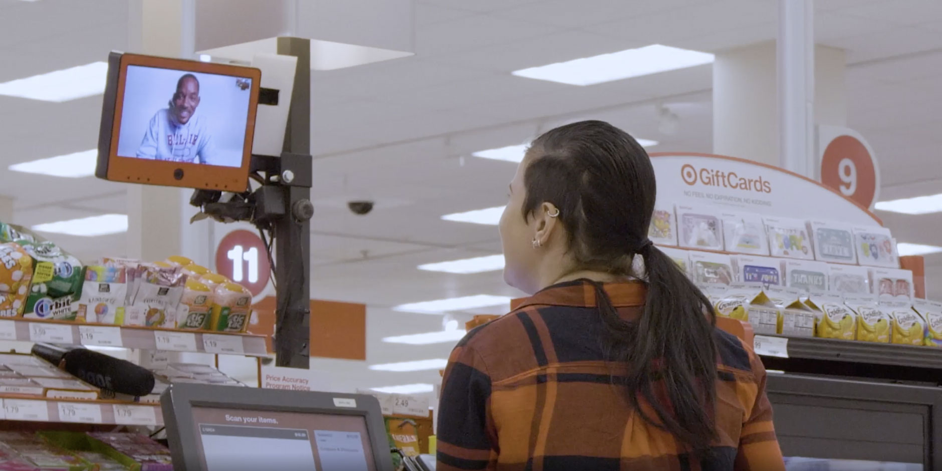 A woman smiles at a self-checkout screen, where Will Smith has magically appeared