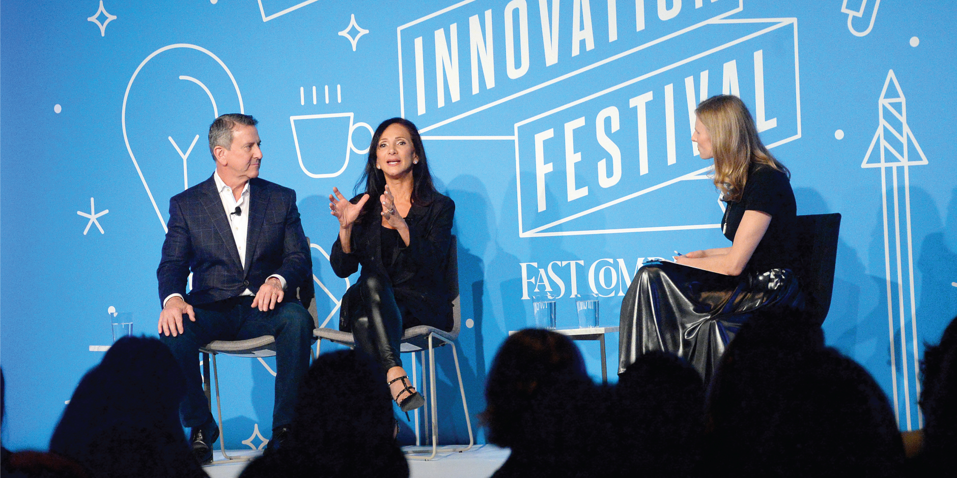 Brian Cornell and Ellen Latham sit in chairs onstage against a blue background in front of a crowd