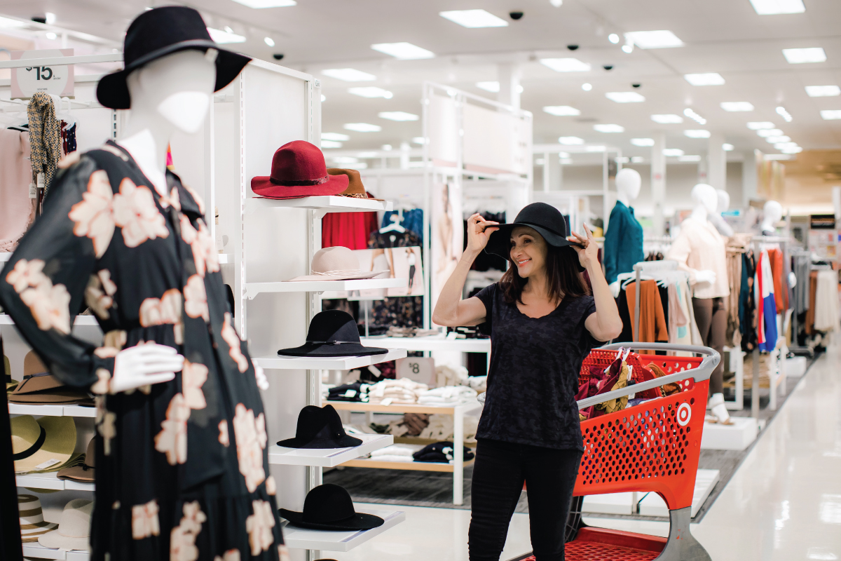 Ellen stands in Target's apparel section trying on a hat next to her red shopping cart filled with products