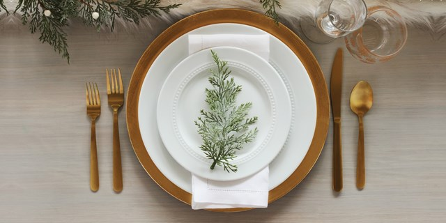 A gold and white place setting with a sprig of faux greenery