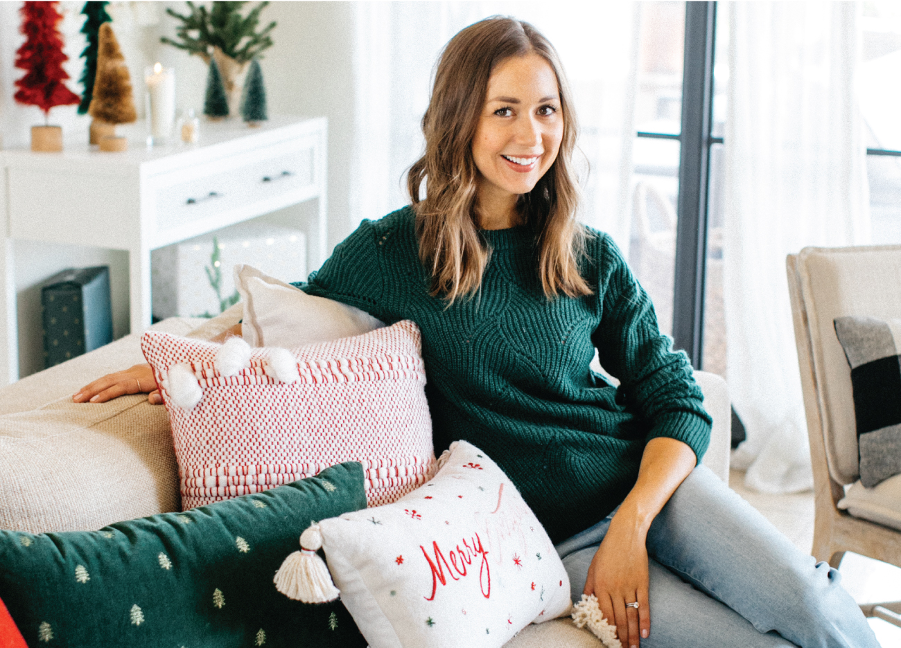 Camille Styles smiles while sitting in a festive living room setting