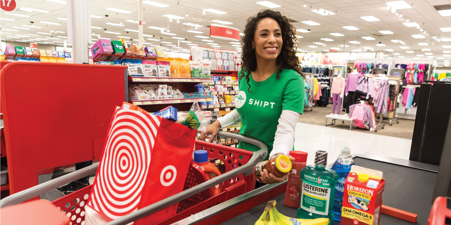A woman in a green Shipt shirt pushes a red cart full of essentials through a Target checkout lane