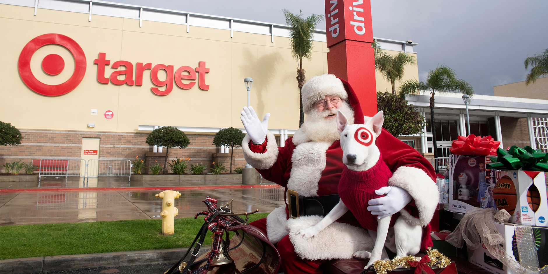 Santa and Bullseye the dog sit in a sleigh in Target's parking lot