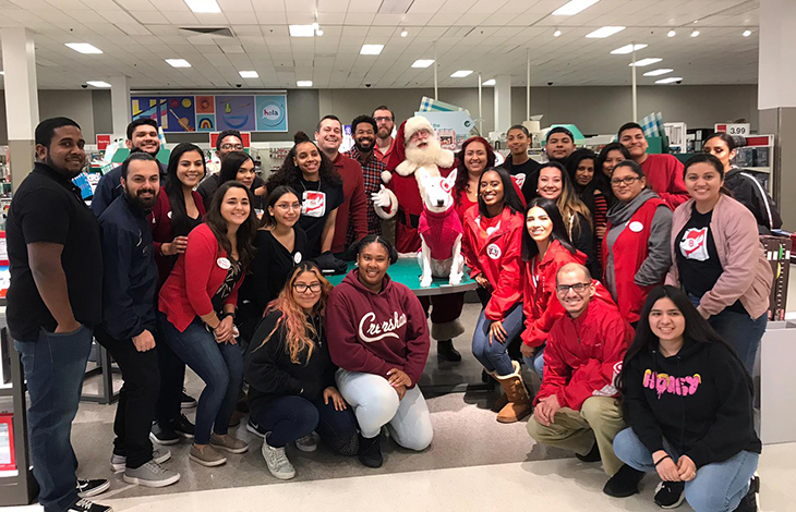 A large group of team members pose with Bullseye and Santa