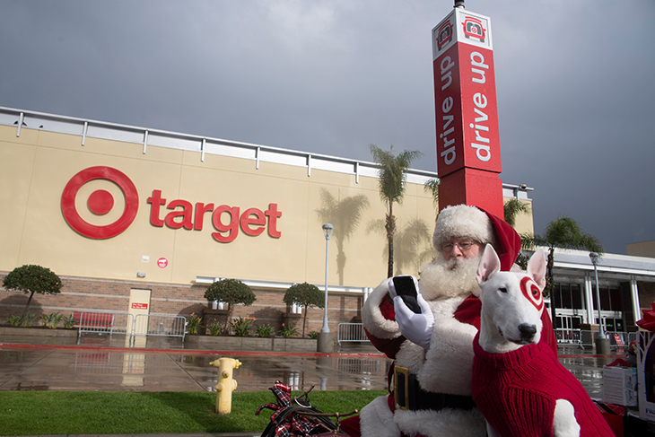 Santa and Bullseye sit in a sleigh in Target's parking lot