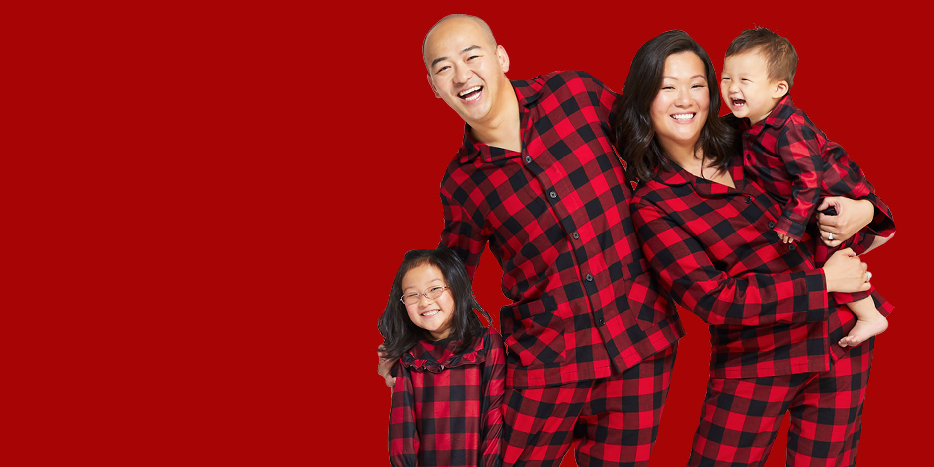 A family in matching buffalo check pajamas