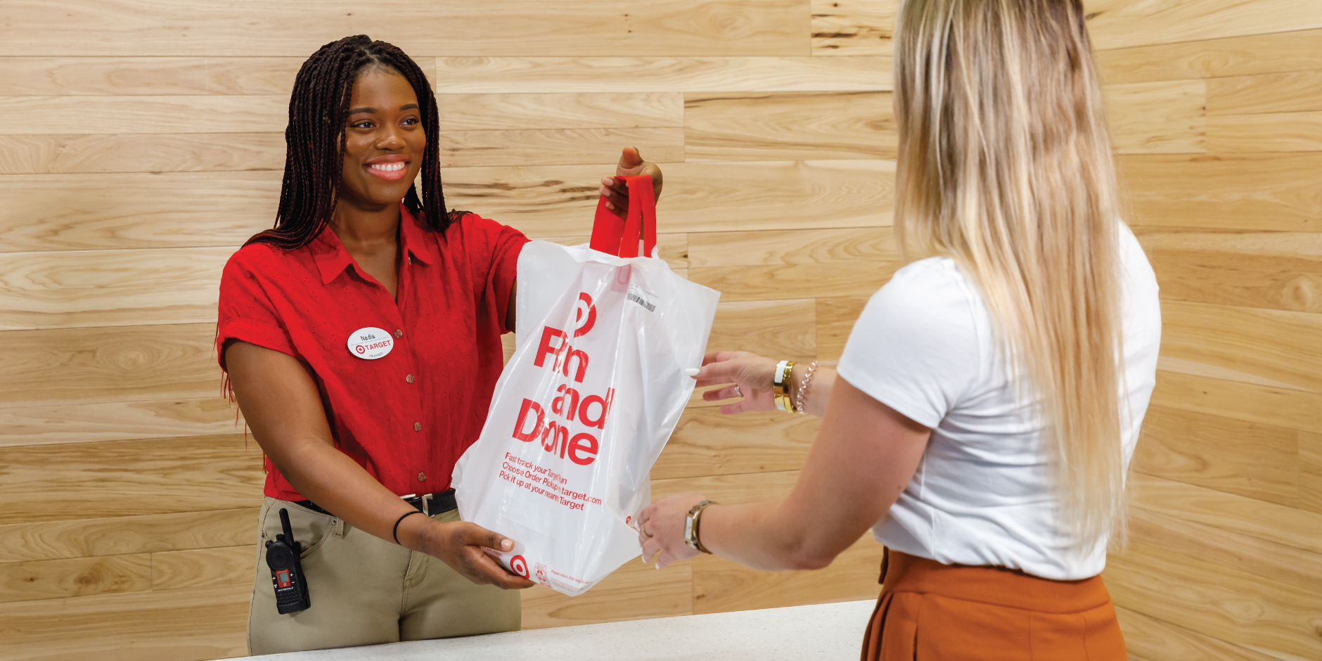 A team member wearing red and khaki hands a bag over a counter to a guest