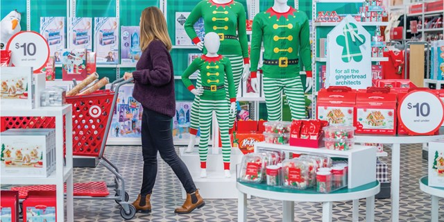 A woman pushes a red cart through a festive Target display, including elf family jammies