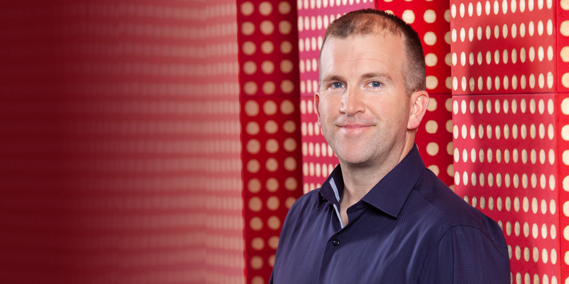 A head-and-shoulders shot of Michael Fiddelke, in a blue shirt against a red & white dot background