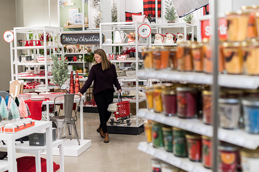 A guest shops with a basket among displays of holiday candles and other festive decor