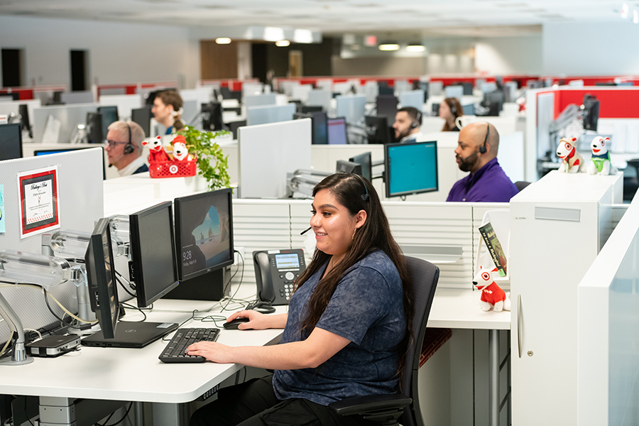 Team members sit in cubicles working on computers and speaking to guests on headsets