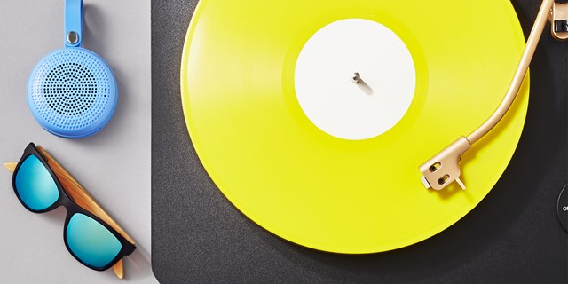 A turntable with a yellow record next to a pair of sunglasses and blue headphones