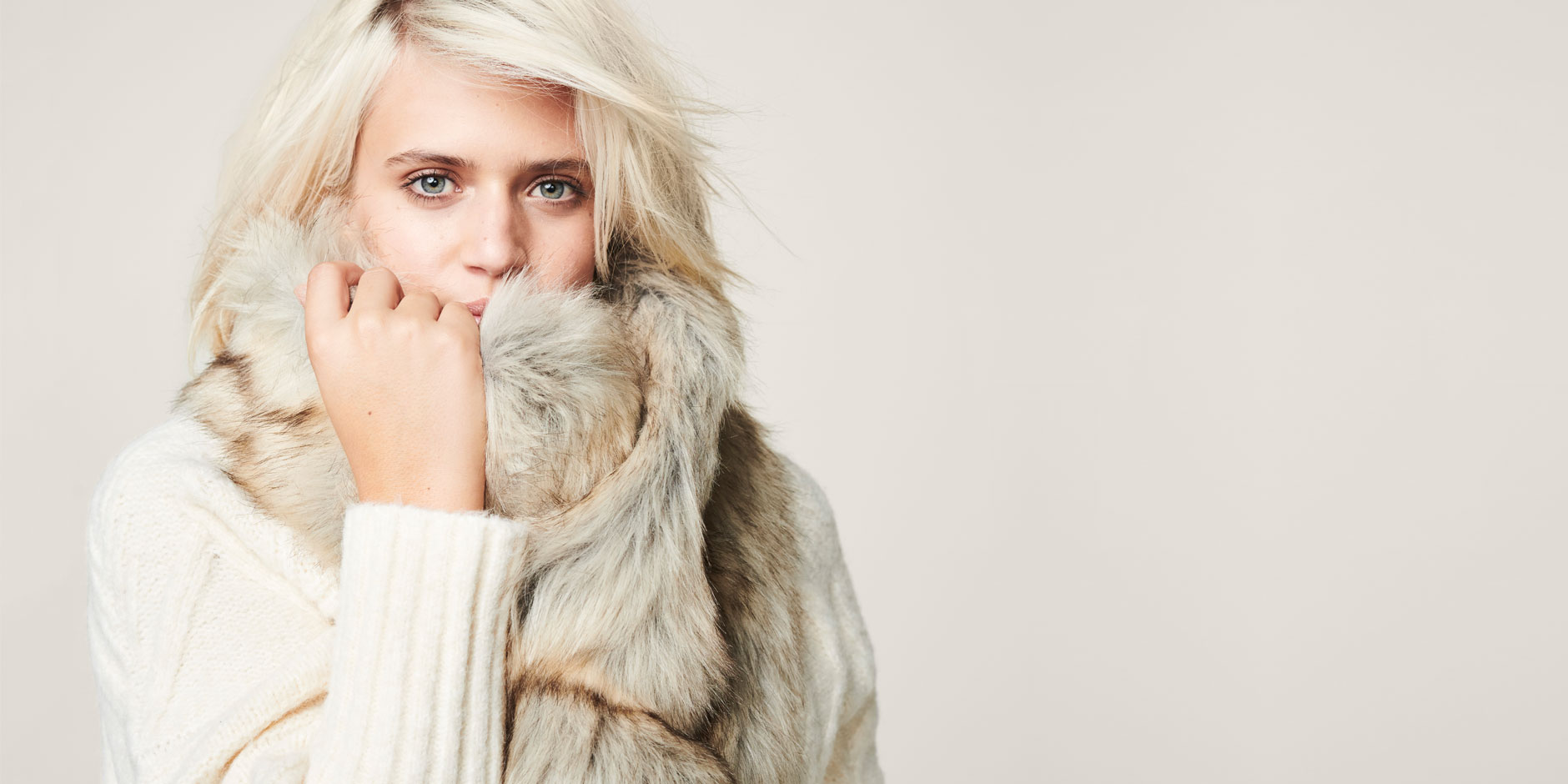 woman with blonde hair wrapped in faux fur scarf and white sweater