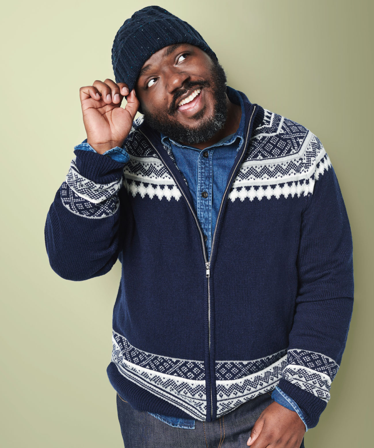 black man with beard wearing navy blue hat, blue zip-up sweater and denim shirt
