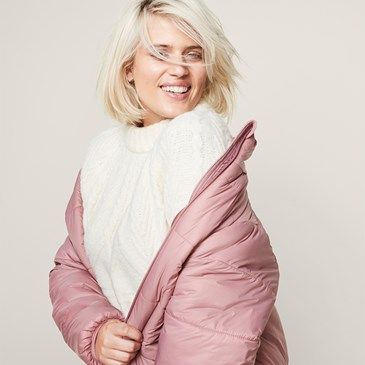 woman with blonde hair in white sweater and pink puffer jacket