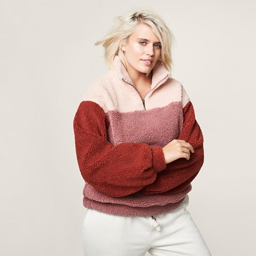woman with blonde hair in red/pink/cream striped sherpa sweatshirt and white jogger pants